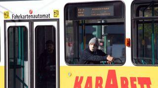 Ein Mann mit Atemschutzmaske und Mütze sitzt in einer leeren Straßenbahn, die durch die Potsdamer Innenstadt fährt (Bild: dpa / Sören Stache)