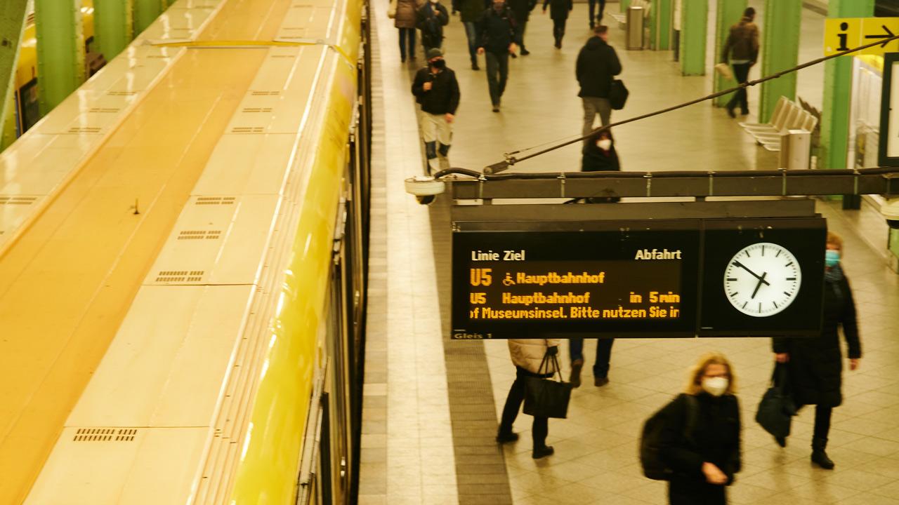 Menschen laufen am Bahnsteig des Alexanderplatz während eine U-Bahn in den Bahnhof einfährt (Bild: dpa)