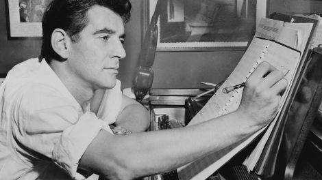 Leonard Bernstein am Klavier, Notizen auf einem Notenblatt machend, 1955; © dpa/Everett Collection