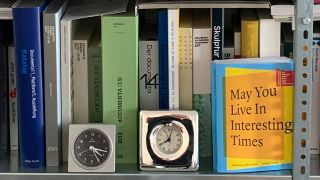 "Wecker und Buch ""May You Live In Interesting Times"" im Regal ; © Silke Hennig"