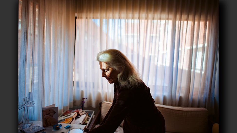 Senior Love Triangle - Standing in her apartment at the retirement home, Jeanie prepares to meet Will and Adina; © Isadora Kosofsky