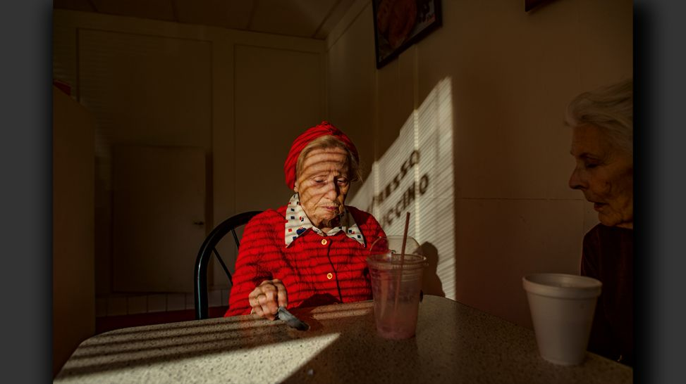 Senior Love Triangle - Adina, holding a bird's feather she found, sits beside Jeanie at the donut shop; © Isadora Kosofsky