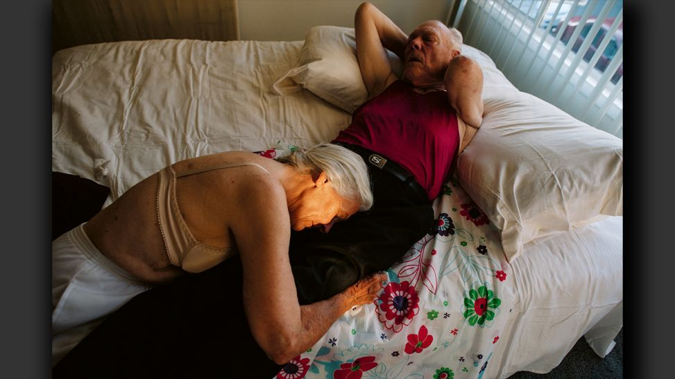 Senior Love Triangle - Jeanie rests her head on Will, as they recline on his bed; © Isadora Kosofsky