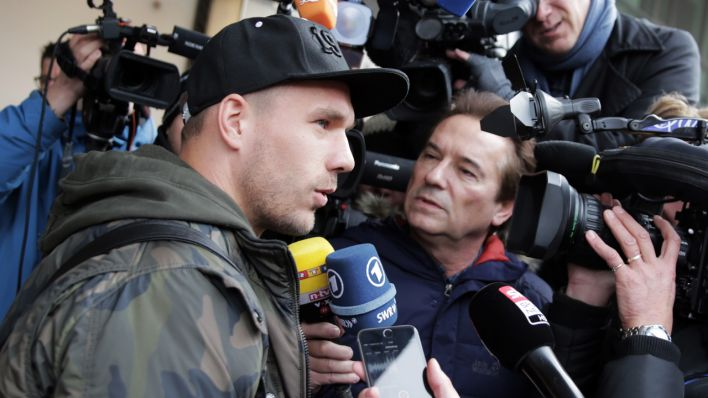 Nationalspieler Lukas Podolski (l) kommt am 22.03.2016 beim Grand Hyatt Hotel in Berlin an und gibt ein Interview (Quelle: picture alliance / dpa)