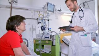 Sven Jungmann, Assistenzarzt Pneumologie, Helios Klinikum Emil von Behring, Berlin-Zehlendorf beim Besuch einer Patientin