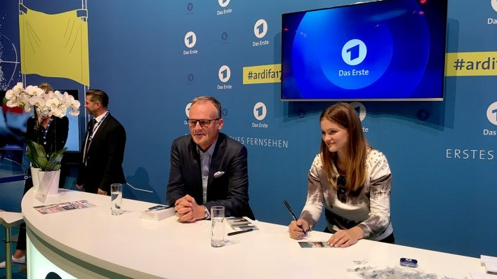 Greta Goodworth und Frank Plasberg am Autogrammcounter (Quelle: rbb)