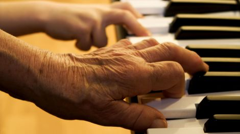 hands of old piano player and grandchild (Quelle: Adobe Stock)