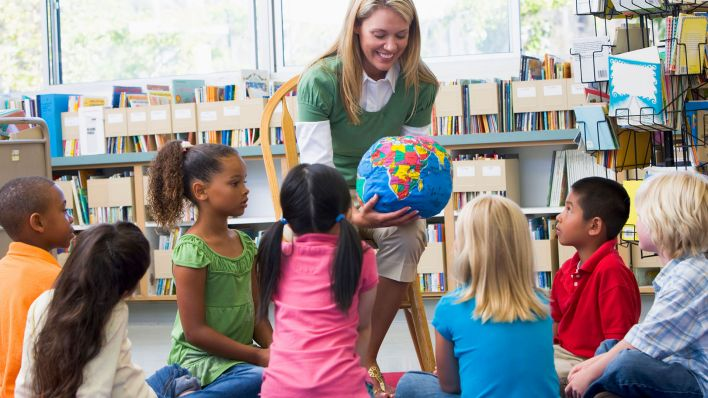 Kindergarten teacher and children looking at globe in library (Quelle: Colourbox)
