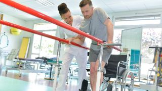 Physiotherapeut hilft Patienten bei Gehtraining (Quelle: Colourbox)