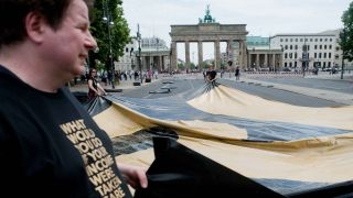 "Freiwillige Helfer legen am 29.05.2016 auf der Straße des 17. Juni zwischen der Siegessäule und dem Brandenburger Tor in Berlin Plakate aus, auf denen in riesigen Lettern ""WHAT WOULD YOU DO IF YOUR INCOME WERE TAKEN CARE OF?"" zu lesen ist (Quelle: dpa)"