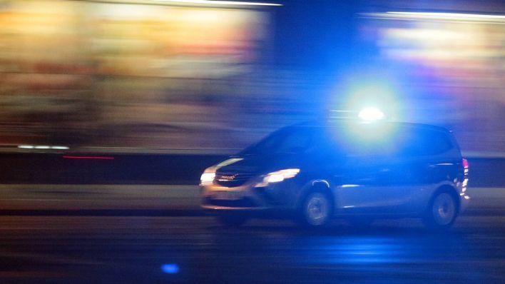 Ein Einsatzwagen der Polizei fährt mit eingeschaltetem Blaulicht durch Berlin (Quelle: imago/Ralph Peters)