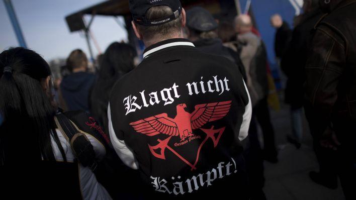 """Ein Demonstrant mit einem T-Shirt mit dem Aufdruck """"Klagt nicht, kämpft, deutscher Bestrafung"""" auf einer rechten Merkel Muss Weg-Demo am 24.3.2017 in Berlin.  (Quelle: imago)"""