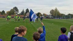 Kinder schwenken eine Fahne, im Hintergrund läuft die Mannschaft