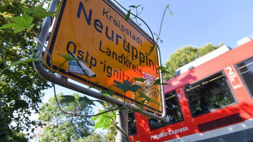 Ortsschild der Kreisstadt Neuruppin, im Hintergrund fährt ein Regionalzug vorbei (dpa/Kalaene) | dpa/Jens Kalaene