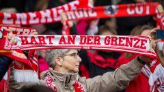 """Weiblicher Fan des FC Energie Cottbus hält einen Fanschal mit der Aufschrift """"Hart an der Grenze"""" hoch. (Quelle: dpa/Fotostand/Weiland)"""