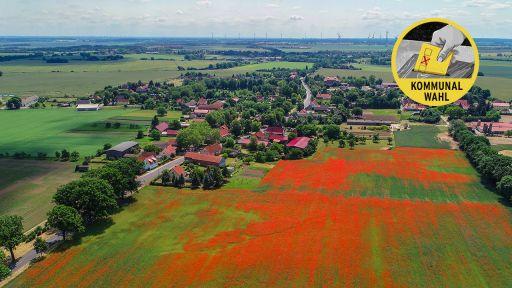 Collage: Eine Luftaufnahme von Friedersdorf im Landkreis Märkisch-Oderland mit einem Sticker zur Kommunalwahl (Bild: dpa/Patrick Pleul | Collage: rbb24) | dpa/Patrick Pleul | Collage: rbb|24