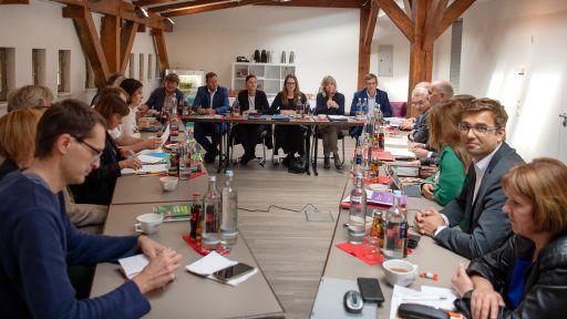 Vertreter der Parteien Grüne (links), Linke (hinten) und SPD (rechts) sitzen vor Beginn der Sondierungsgespräche über eine mögliche Koalition im Sitzungsraum. (Quelle: dpa/Monika Skolimowska) | dpa/Monika Skolimowska