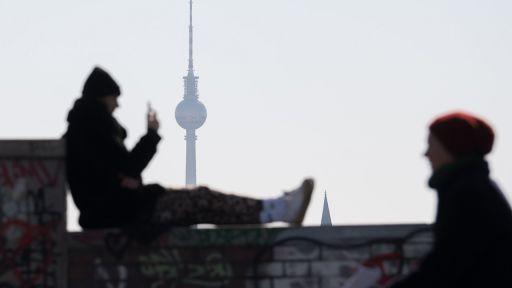 Ein Mann genießt das schöne Wetter und sitzt auf einer Mauer und schaut auf sein Smartphone, im Hintergrund steht der Fernsehturm. (Quelle: dpa/Jörg Carstensen) | dpa/Jörg Carstensen
