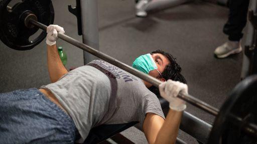 Ein Mann mit Mundschutz und Einmalhandschuhen trainiert in einem Fitnessstudio (Quelle: dpa/Marius Becker). | dpa/Marius Becker