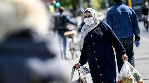 Eine Frau trägt ihre Einkäufe mit einem Nasen-Mund-Schutz (Bild: dpa/Britta Pedersen) | dpa/Britta Pedersen