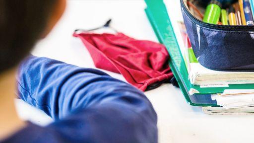 Symbolbild: Eine Mund-Nasen-Bedeckung liegt während einer Unterrichtsstunde einer fünften Klasse neben einem Mäppchen und Schulbüchern auf einem Schultisch. (Quelle: dpa/Marijan Murat)   dpa/Marijan Murat