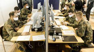 Soldaten des Wachbataillons beim Bundesministerium der Verteidigung werten am 02.06.2020 im Gesundheitsamt Berlin-Mitte an Computern die Daten zur Corona-Kontaktverfolgung aus. (Quelle: dpa/Carsten Koall)