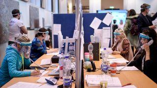 Mitarbeiter des Gesundheitsamtes Mitte mit Gesichtsschutzschirm telefonieren im Lagezentrum des Gesundheitsamt Mitte.
