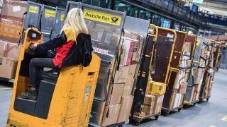 Eine Frau fährt Pakete durch das DHL-Paketzentrum in Rüdersdorf, Archivbild (Quelle: DPA/Patrick Pleul)