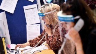 Berlin: Mitarbeiter des Gesundheitsamtes Mitte mit Gesichtsschutzschirm telefonieren im Lagezentrum des Gesundheitsamt Mitte. Quelle: dpa/Britta Pedersen
