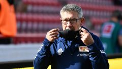 Union-Trainer Urs Fischer setzt sich eine Maske auf (Quelle: imago images/Bernd König)