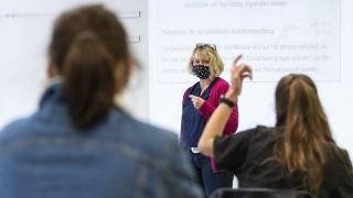 Schuelerinnen einer 10. Klasse beim Unterricht, durch Corona bedingt mit Maske (Quelle: dpa/Stephan Goerlich)