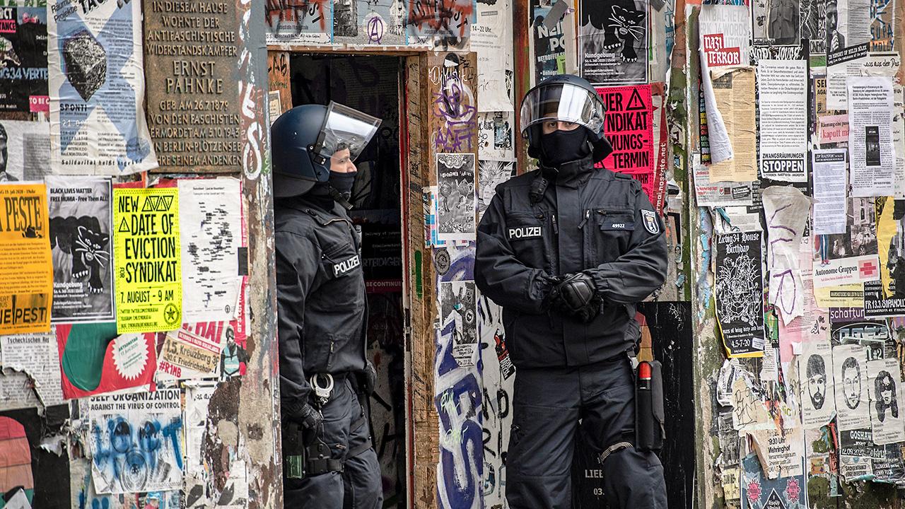 Polizeibeamte stehen im Eingang eines Hauses in der Rigaer Straße. (Quelle: dpa/Paul Zinken)