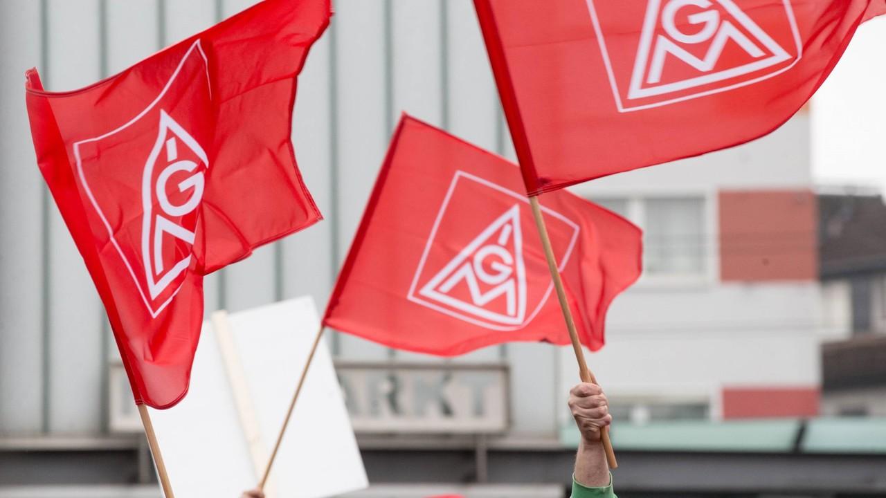 Streikende schwenken Fahnen der IG Metall Warnstreik IG Metall (Bild: imago images/Deutzmann)