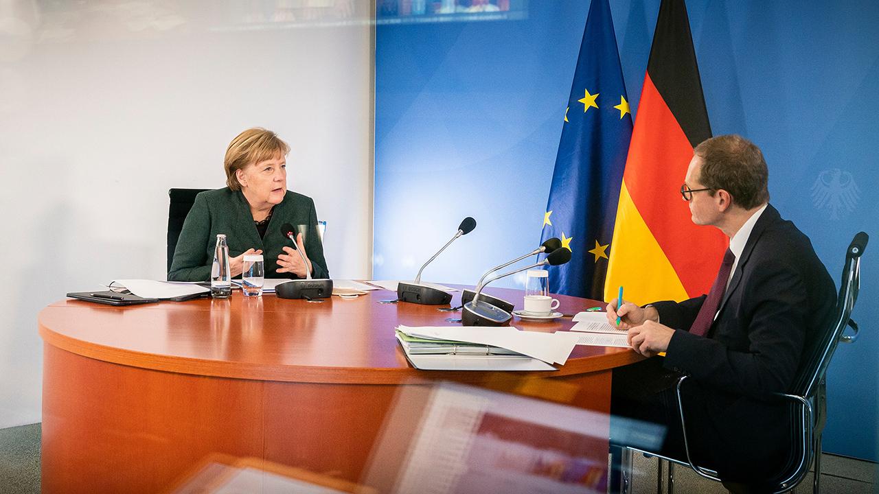 Bundeskanzlerin Angela Merkel (CDU) und Michael Müller, Regierender Bürgermeister von Berlin, sitzen im Bundeskanzleramt gemeinsam bei der Videokonferenz mit den Ministerpräsidentinnen und Ministerpräsidenten der Länder zur Corona-Situation. (Quelle: dpa/S. Kugler)