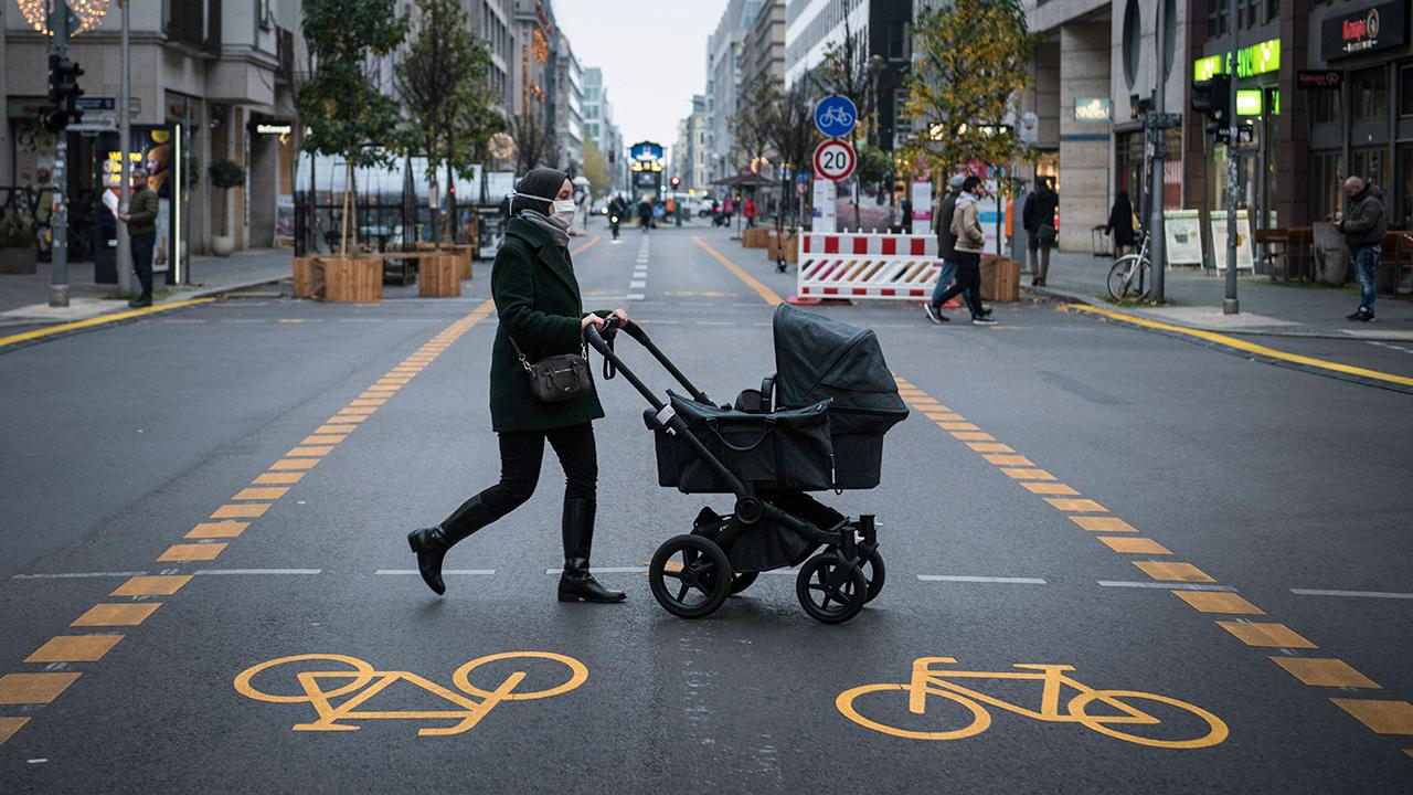 Eine Passantin mit Kinderwagen ueberquert den Radweg in der Friedrichstrasse in Berlin Mitte (Bild: imago images/Bildgehege)
