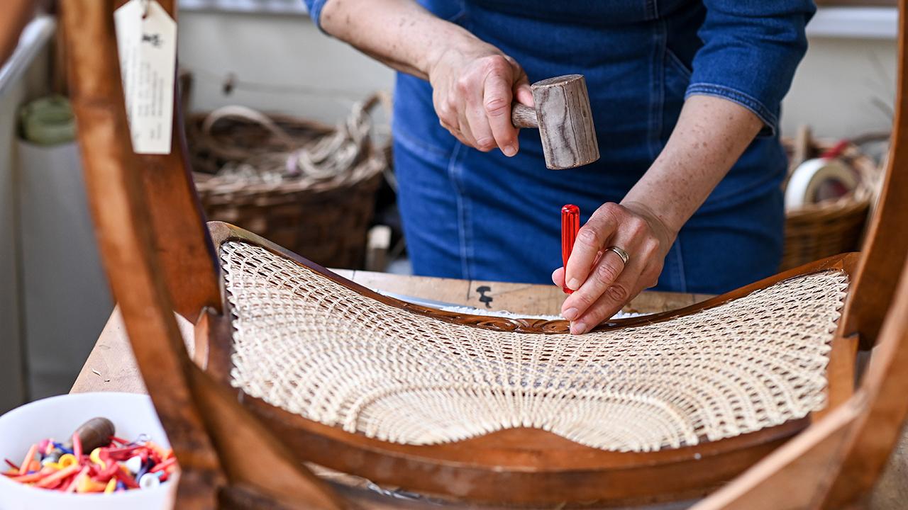 Stuhlflechterin Silke Schlittermann arbeitet am 12.05.2021 in ihrer Werkstatt in Köpenick an der Reparatur eines Sessels mit Halbsonnengeflecht. (Quelle: dpa/Jens Kalaene)