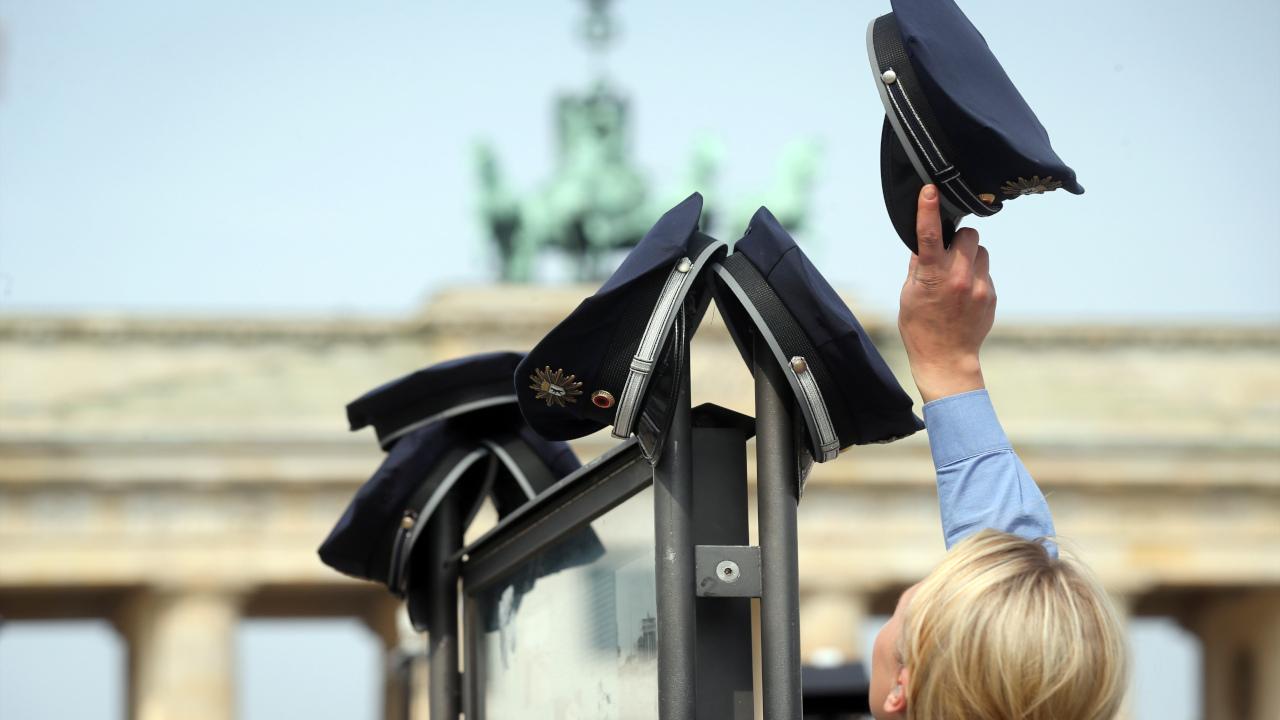Mützen der Berliner Polizei hängen an einer Informationstafel in Berlin vor dem Brandenburger Tor (Quelle: dpa/Kay Nietfeld)