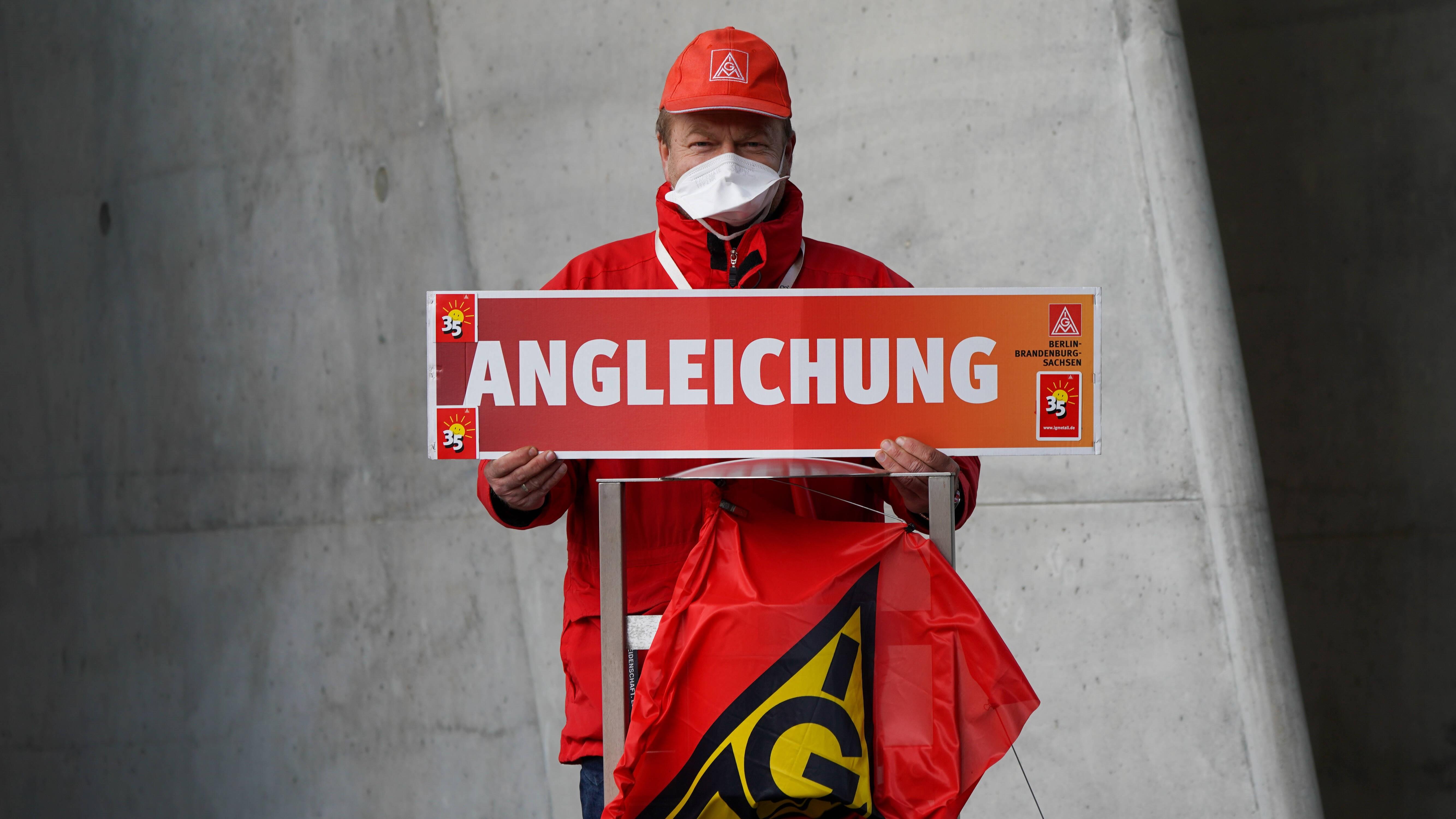 """Ein unbekannter IG-Metall-Aktivist hält ein Schild hoch mit der Forderung """"Angleichung"""""""