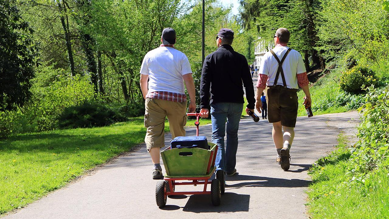 Symbolbild: Drei Männer sind am Vatertag mit Bier, Bollerwagen und Musik unterwegs. (Quelle: imago images)