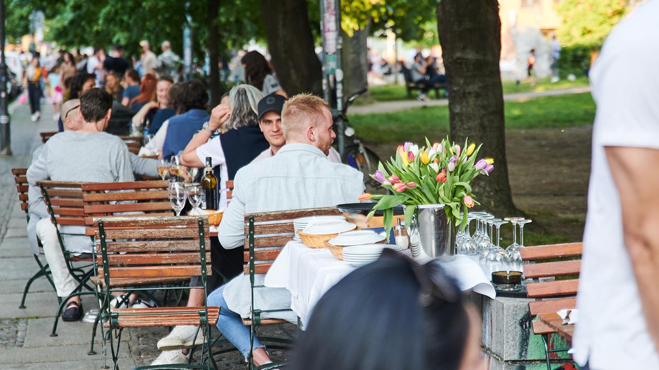 """Viele Menschen sitzen draußen im Restaurant """"SIMON"""" in Berlin Mitte (Bild: dpa/Annette Riedl)"""