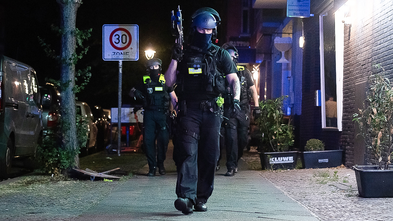 Symbolbild: Ein bewaffneter Polizeibeamter geht in Richtung Müllerstraße. (Quelle: dpa/Paul Zinken)