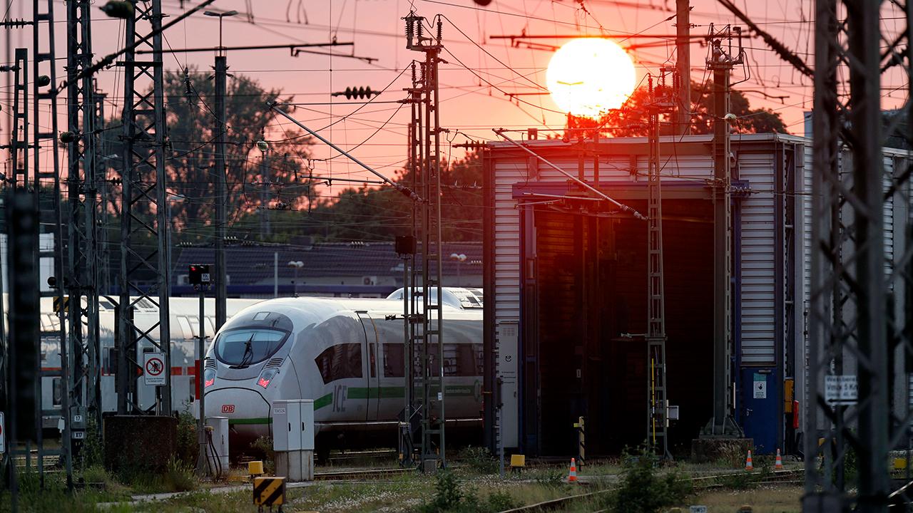 Symbolbild: Mehrere Züge stehen bei Sonnenuntergang neben einer Wartungshalle