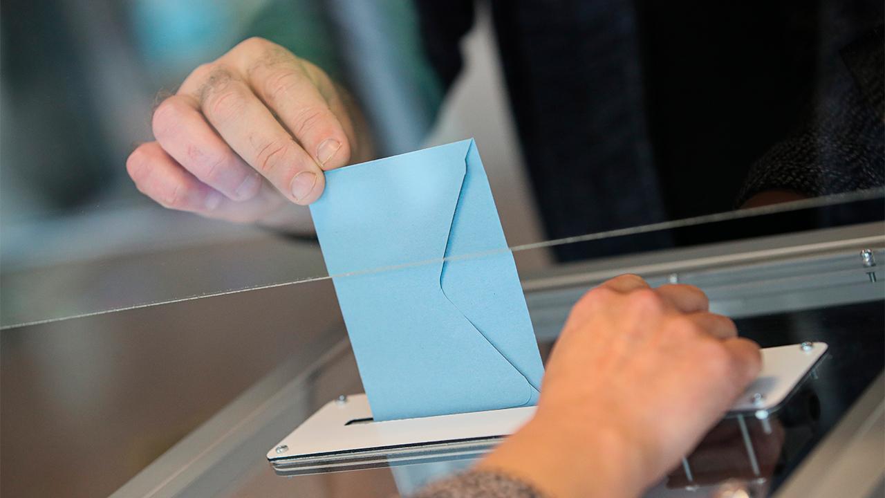 Ein Wähler wirft seinen Stimmzettel in einem Wahllokal in eine Wahlurne (Bild: dpa/David Vincent)