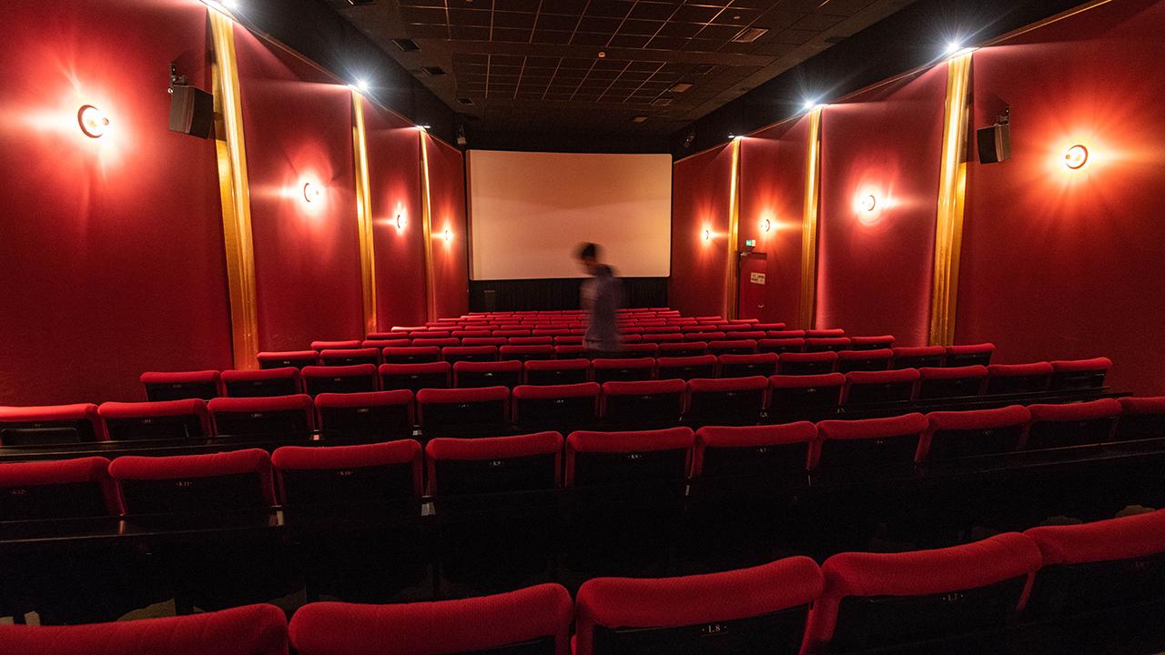 Ein Mitarbeiter reinigt einen Kinosaal. (Quelle: dpa/Nicolas Armer)