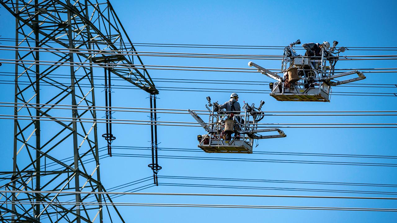 Symbolbild: Zwei Monteure arbeiten an einer Hochspannungsleitung in Nordrhein-Westfalen (Bild: dpa/Jochen Tack)