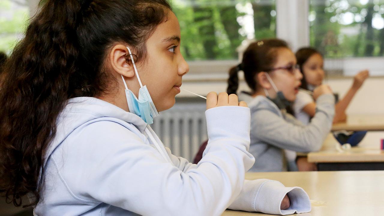 Archivbild: Schülerinnen einer Grundschule machen einen Corona-Lolli-Test. (Quelle: dpa/R. Weihrauch)