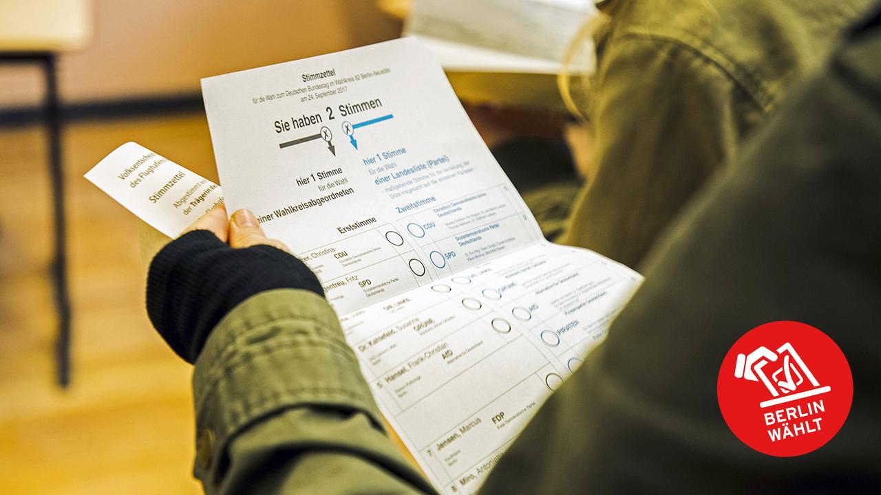 Eine Frau haelt den Stimmzettel fuer die Bundestagswahl in einem Wahllokal (Bild: imago images/Emmanuele Contini/Colourbox)
