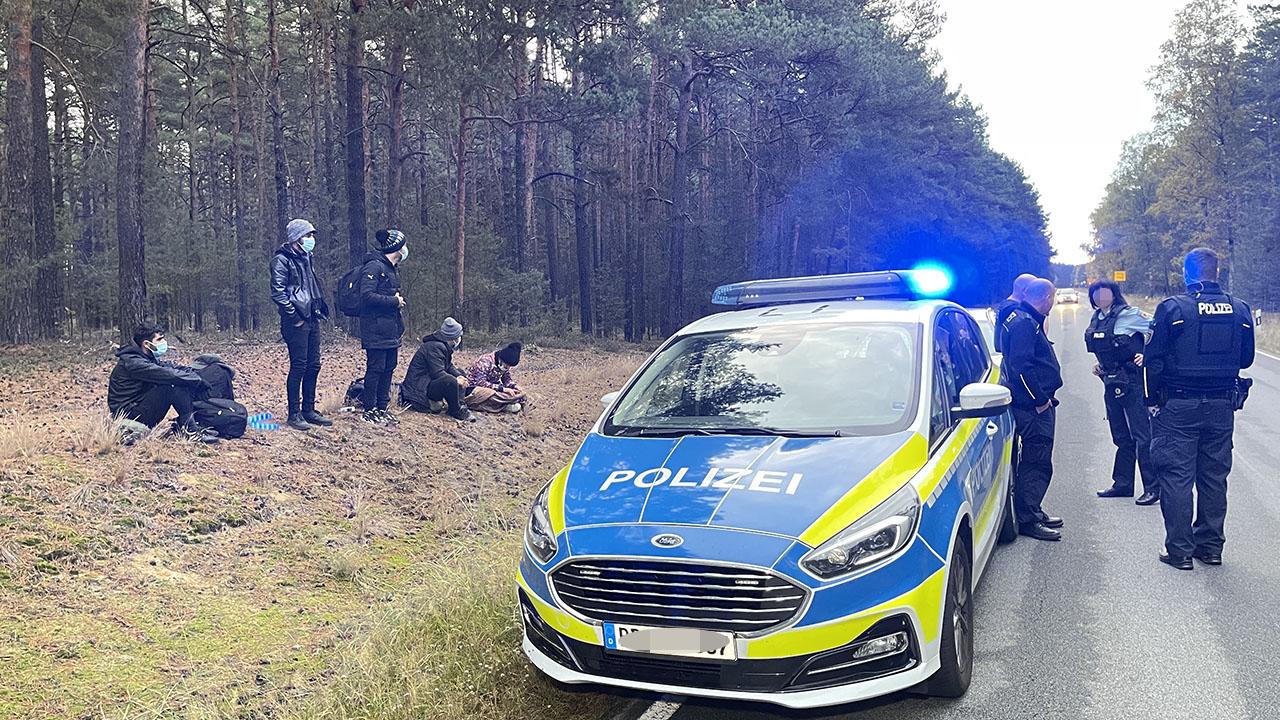 Bundespolizisten stehen neben einer Gruppe von Migranten, die zuvor über die deutsch-polnische Grenze gegangen waren. (Quelle: dpa/Danilo Dittrich)